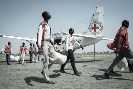 """Des volontaires de la Croix-Rouge du Soudan du Sud et des employés du CICR déchargent du matériel de pêche d'un avion du CICR. South Sudan Red Cross volunteers and ICRC staff unload fishing kits from a plane for a distribution to take place that day. Site web du CICR, article du 27 juillet 2015 : """"Les déplacements, l'insécurité, les inondations et de nombreux autres problèmes empêchent beaucoup de Soudanais de produire ou d'obtenir de quoi s'alimenter. Ces problèmes sont aggravés par la reprise des combats qui ont déplacé des milliers de personnes, les empêchant de cultiver leurs terres et leur coupant l'accès aux marchés. Marijka Van Klinken est nutritionniste. Elle nous explique en quoi a consisté l'action menée par le CICR jusqu'à présent. Que fait le CICR face à l'insécurité alimentaire ? Dans sa lutte contre l'insécurité alimentaire, le CICR donne la priorité à la prévention, son assistance devant améliorer la sécurité alimentaire de la population avant que celle-ci ne connaisse la malnutrition, et dans les cas où il y a déjà malnutrition, à en réduire la prévalence autant que possible et à augmenter la résilience de la population. L'action préventive du CICR consiste donc à distribuer des vivres dans les situations d'urgence et à fournir aussi des semences quand une solution durable est possible et envisageable. À ce jour, le CICR a déjà distribué plus d'un million de rations alimentaires pour un mois dans plusieurs des régions les plus touchées du pays, et il a également fourni des semences et des outils à près de 400 000 personnes. Du fait de la récente intensification des combats et de l'augmentation de l'insécurité, l'accent devra nécessairement être mis à court terme sur l'aide d'urgence et la distribution de rations alimentaires. Comment procède le CICR dans de tels cas ? Au Soudan du Sud, des distributions de rations alimentaires ont été effectuées sur la base de notre évaluation des besoi"""